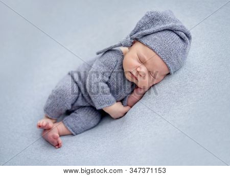 Charming newborn in knitted suit and hat resting on side