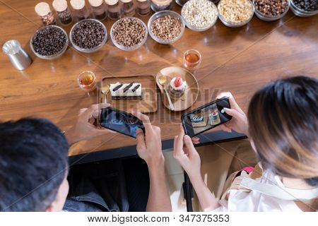 Top view of two Bloggers of young adult asian owner entrepreneur review cafe coffee shop for social media and online marketing in cafe. Using for startup of small business maketing and consumerism.