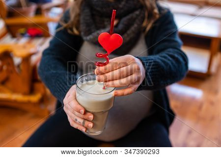 A Close Up View Of A Heavily Pregnant Lady Holding A Healthful Pureed Drink With Novelty Valentine S