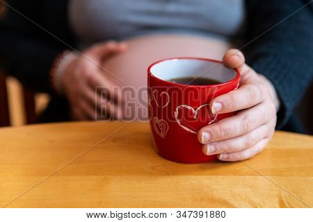 A Selective Focus View Of A Pregnant Girl Sitting At A Wood Table With Cup Of Coffee In Novelty Vale