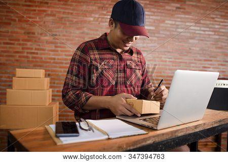 A Young Asian Man Starts A Small Business Owner Writing An Address On A Cardboard Box At Work. Indep