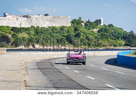 Pink Old Cabriolet Rides Along The Malecon Embankment Against The Background Of The Old Fort. El Mor