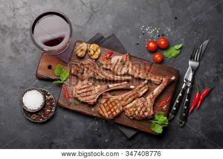 Grilled lamb ribs on cutting board and red wine glass. Hot rack of lamb with spices and condiments. Top view