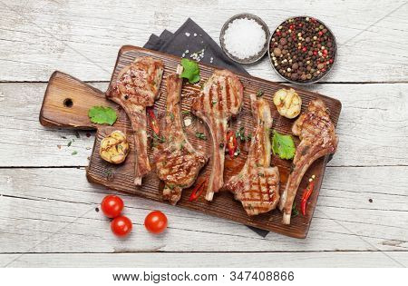 Grilled lamb ribs on cutting board. Hot rack of lamb with spices and condiments. Top view on wooden table