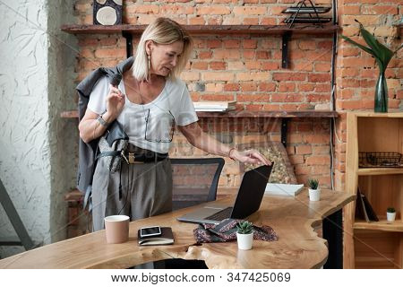 Mature businesswoman with jacket on shoulder shutting down laptop while leaving office