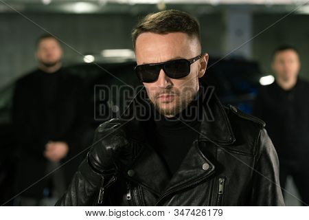 Male spy or gangster in sunglasses, black leather gloves and jacket and his gang or bodyguards on background
