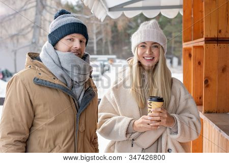 Happy young heterosexual couple in casual winterwear standing by wooden stall and looking at you while chilling out