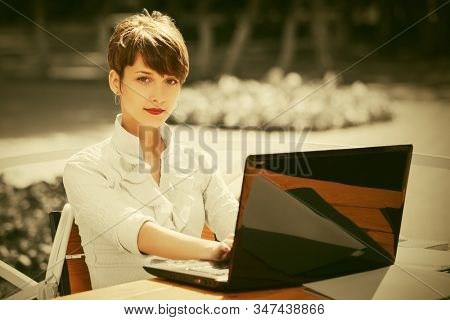 Young business woman using laptop at street cafe Stylish fashion female model in white shirt with pixie hair style
