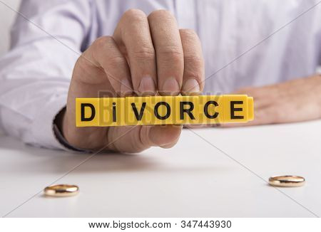 Husband Hand Holding Word Divorce And Two Engagement Rings On Table, Divorcement