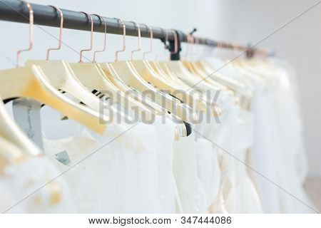 Clothing rack with wedding dresses on golden hangers in row, wedding show room concept