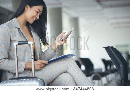 Business Women Sit And Wait At Passenger Boarding Terminal In Airport,luggage And Suicase Bag On The