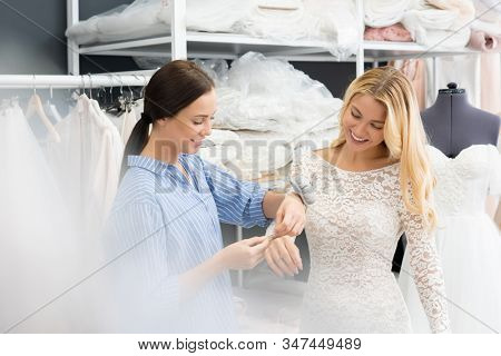 Positive young female tailor adjusting sleeve of wedding dress while blond bride fitting it in sewing workshop