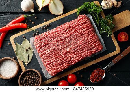 Spices And Cutting Board With Minced Meat On Wooden Background, Top View