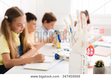 Modern Technologies. Children Learning In Class With Humanoid Robotic Hand On Foreground, Panorama