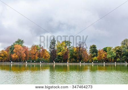 Beautiful Large Lake And Colorful Autumn Trees In The Buen Retiro Park Near The Monument To Alfonso