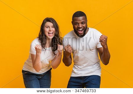 Lucky Win. Overjoyed Interracial Couple Celebrating Success Together, Raising Fists With Excitement