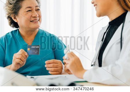 Joyful Senior Asian Female Patient In Hospital Attire Giving Credit Card To Female Doctor For Paymen