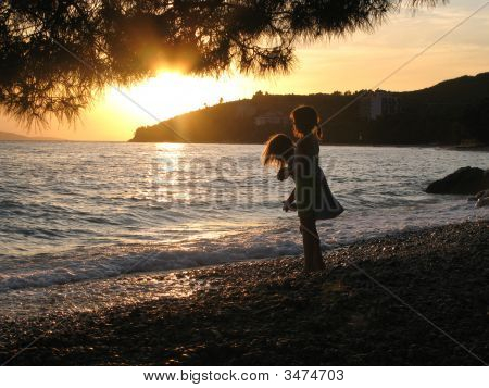 Two Little Girls Playing On Beach In Sunset, Tucepi, Croatia
