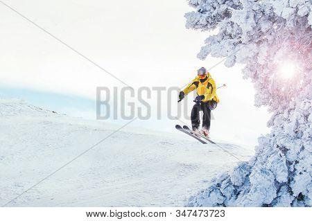 Mountain Skier In Alp Mountains Doing Some Ski  Jumping. Ski Mountain Sport.
