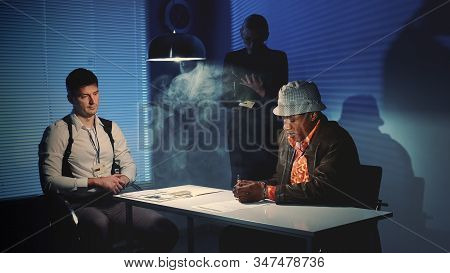 Suspected Mixed-race Man Signing A Document Of Accusation. Interrogation Room In Smoke.