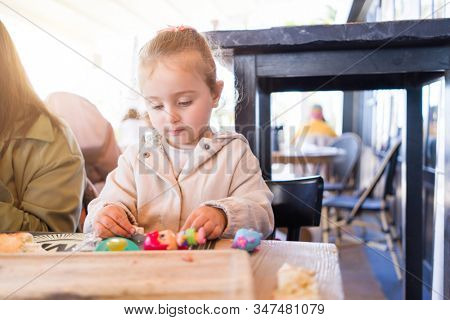 Beautiful toddler child girl sitting on baby highchair  playing with toys on the table