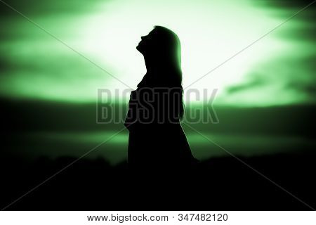 Youth Woman Soul At Green Sun Meditation Dreaming Past Times. Silhouette In Front Of Sunset Or Sunri
