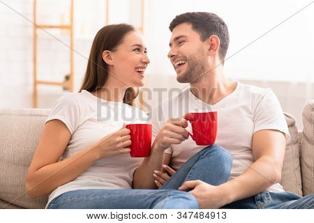 Morning Coffee. Happy Couple Talking And Laughing Having Hot Drinks Sitting On Couch At Home. Select