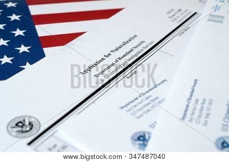 N-400 Application For Naturalization Blank Form Lies On United States Flag With Envelope From Depart