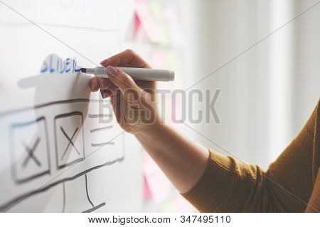 Female Web Developer With Marker Sketching Website On Whiteboard