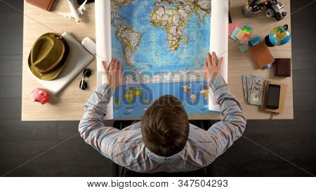 Male Unfolding World Map To Choose Country For Travel Destination, Vacation
