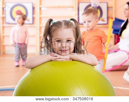 Smiling Pretty Child With Fitness Ball In Gym. Gym Class For Preschool Kids In Kindergarten