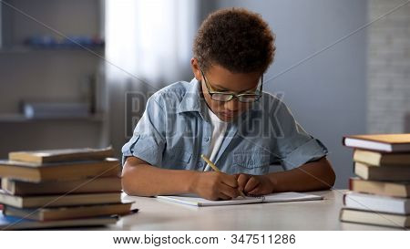 Smart Little Boy Neatly Writing Homework In His Notebook, Diligent Schoolboy