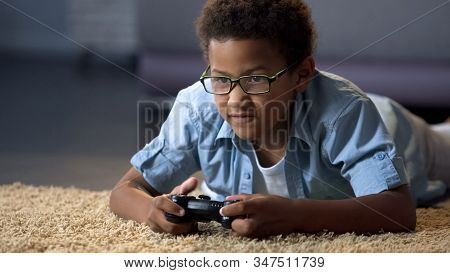 Afro-american Boy Absorbedly Playing On New Video Game Console, Home Activity