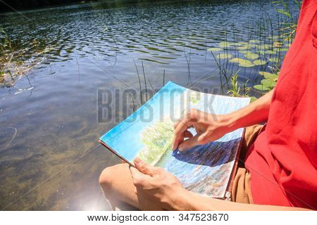 Close-up shot of teenager boy sitting by forest lake drawing landscape with pastel crayons - plein air scetching concept