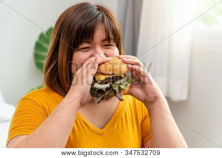Hungry Overweight Young Asian Woman Holding Hamburger, Her Hungry All Time And Overeat, Gluttony And