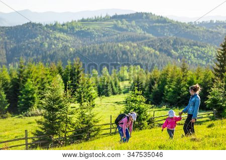 Young Mother And Two Little Daughters Travelers Stand On A Slope With A Gorgeous View Of The Hills C