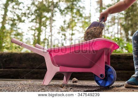 Child Putting Sas In Plastic Pink Toy Wheelbarrow