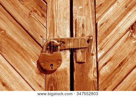 Grungy Wooden Door With Lock In Orange Tone. Abstract Architectural Background And Texture For Desig