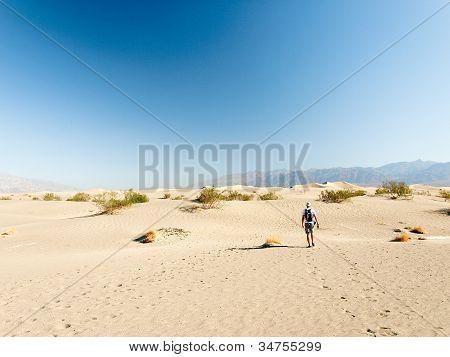 Man walking alone in the desert sand dunes