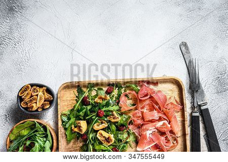 Salad With Parma, Prosciutto Ham, Arugula And Figs. Italian Antipasti. Gray Background, Top View, Sp