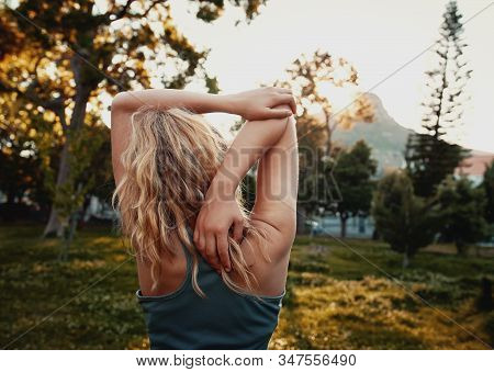 Rear View Of Blonde Young Woman In Sportswear Stretching Her Arm In The Park - Sporty Woman Stretchi