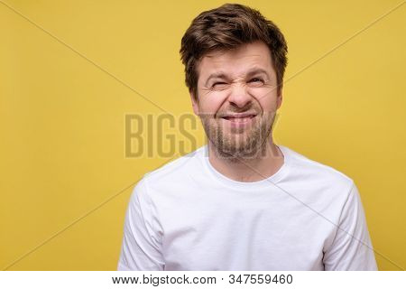 Unsure Caucasian Man In His 30s With Bristle In Casual White T-shirt Frowning And Grimacing