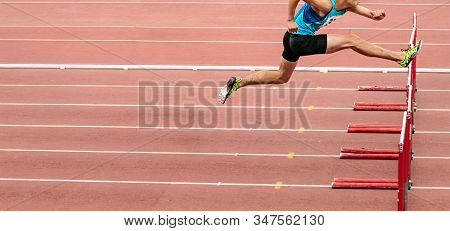 Male Runner Running 110 Meters Hurdles In Athletics Competition