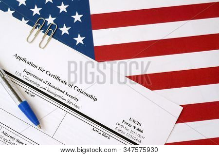 N-600 Application For Certificate Of Citizenship Blank Form Lies On United States Flag With Blue Pen