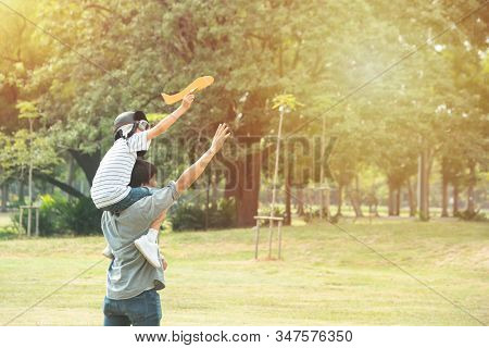 Asian Father And Son Play With Paper Plane In Public Park In Summer , Fatherhood And Kid Have Leisur