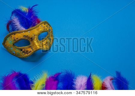 Carnival. Festive Background With Copy Space. Golden Carnival Mask With Colorful Feathers On A Blue