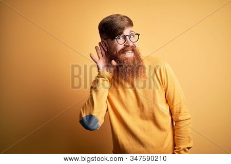 Handsome Irish redhead man with beard wearing glasses over yellow isolated background smiling with hand over ear listening an hearing to rumor or gossip. Deafness concept.
