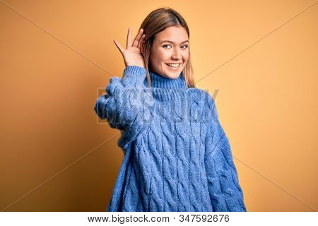 Young beautiful blonde woman wearing turtleneck sweater over yellow isolated background smiling with hand over ear listening an hearing to rumor or gossip. Deafness concept.
