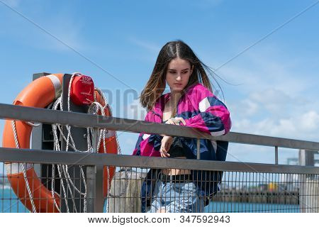 Attractive Teenage Woman Stands Looking Deep In Thought Leaning On Waterfront Railing Next To Orange