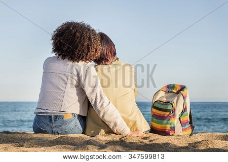 Interracial Lesbian Couple Embracing In Front Of The Sea Next To A Backpack With The Rainbow Flag Co